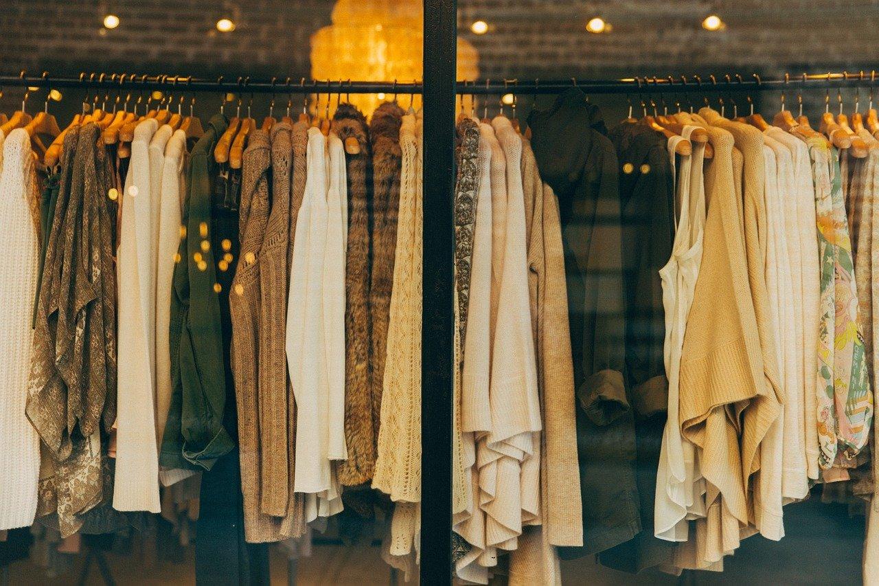 a rack of women's garments is seen through a shop window
