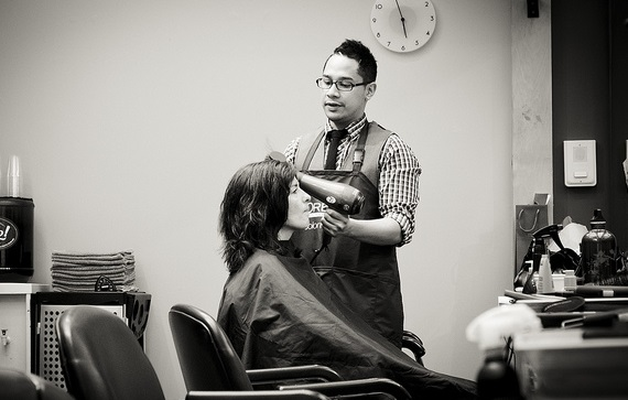 A stylist styling client's hair