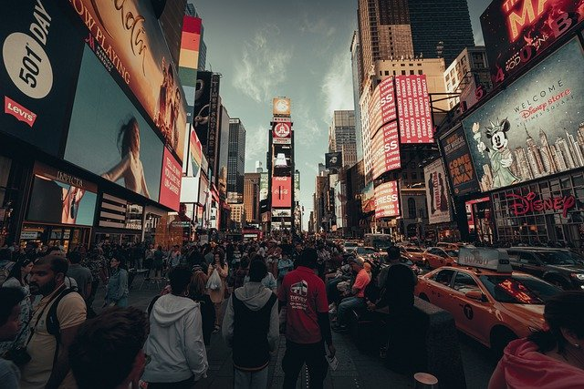 new york city times square street screens advertising to a crowd of people