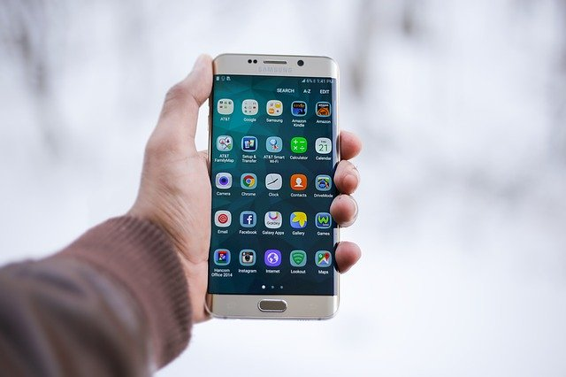 hand holding smartphone with apps on screen